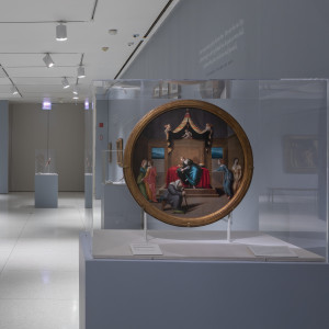 A view of a museum display featuring art on blue walls, as well as a plate displayed in an acrylic case.