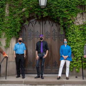 Five people wearing masks pose together on a set of steps with a large wooden door and ivy in the background.