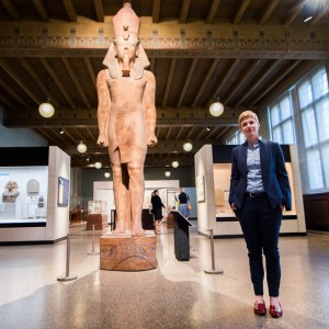 A female-presenting person poses next to a stone model of a pharaoh, both with hands and their sides.