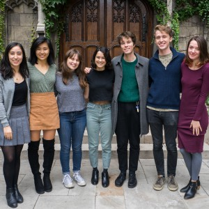 Seven students stand smiling with arms slung over each other's shoulders in front of an ivy-covered door..