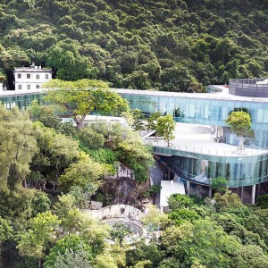 An aerial view of Hong Kong campus, nestled among a forest of trees.