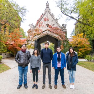 A group of five students stand outside of an arched gate covered with fall foliage.