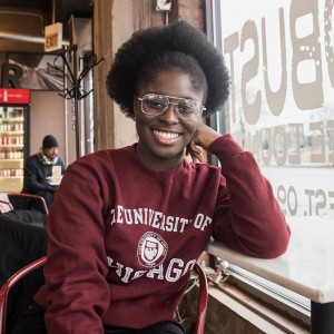 A female-presenting student sits at a small coffee table by the window in a cafe, her elbow propped on the table and cheek resting against the back of her hand. She wears a University of Chicago sweatshirt, and grins for the camera.