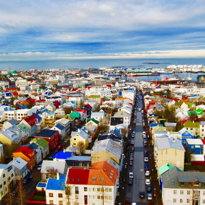 The colorful rooftops of homes are shown with the ocean in the background in a photo of Reykjavik, Iceland