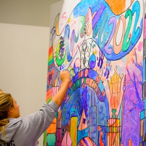 Two students paint a large, colorful mural