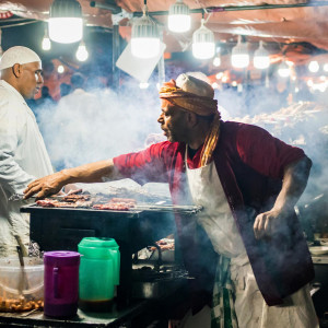 Two male-presenting people cook skewers of meat on a grill underneath a well-lit awning amidst a billow of smoke.