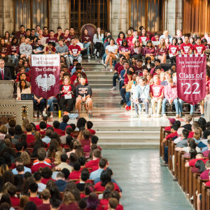 A large group of students sit in the pews of a chapel listening to a speaker. Flags for The College and the Class of '22 are displayed.