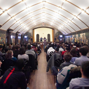 A large audience of students listens to two speakers inside an arched room.
