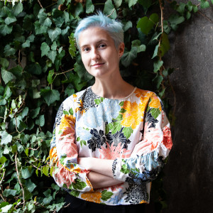 A female student wearing a floral shirt poses in front of a wall covered with green ivy.