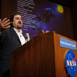 A man stands speaking behind a podium with the NASA logo on it.