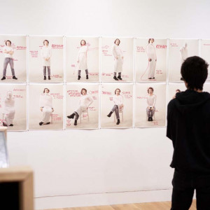 A person views a series of artwork on a white wall.