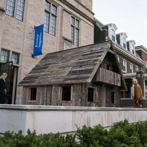 A small hut, made of planks of wood, is shown outside on a the terrace of the Neubauer Collegium.