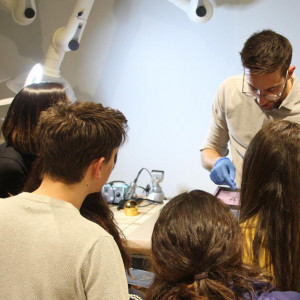 A group of students crowd around a professor looking at an iPad in a lab.