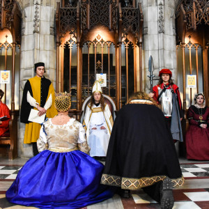Students dressed in renaissance era robes kneel before a student dressed as the Pope inside of a chapel.