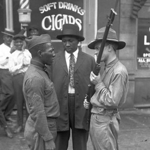 A black and white archival photo is shown two militia members facing off with an African-American veteran on a street during the 1919 Chicago race riots.