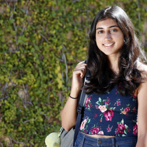 A portrait of Devshi Mehrotra, who smiles and stands in front of a green wall.