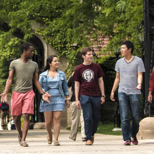 A group of students walk through a gate on a college campus.