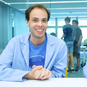 Still from a video of two students facing the camera. Both wear light blue lab coats.