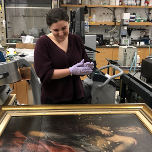 Caroline Longo assesses spots of damaged on a large framed painting. She is surrounded by jars and other lab equipment for conservation analysis.