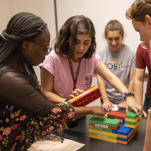 A group of students congregate over a table with large, interlocking lego blocks that form a model of GGRC.