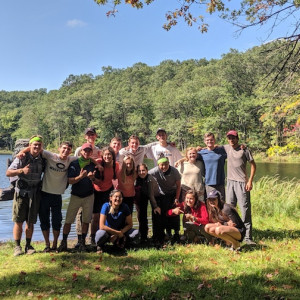 A group of students poses for a photo in front of a lake in a forest.