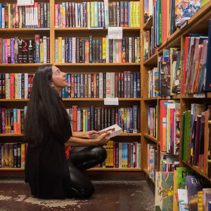 Samira Ahmed squats down while holding a book among bookshelves in a bookstore.