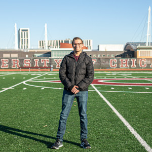 "A student stands on a football field on a sunny day with the words ""University of Chicago"" on a fence in the background."