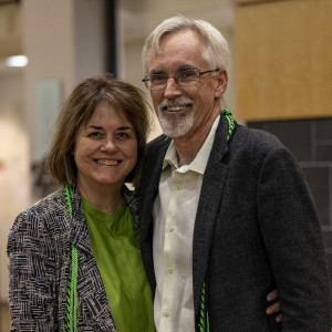 Cathe and Larry McEnerney pose with their arms around each other, smiling warmly in a lounge in GGRC. They wear green graduation cords.