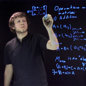 A professor writes math equations with a neon blue marker on a clear board