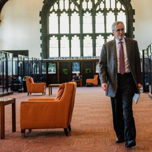 Larry McEnerney walks through an arched room with glass cubicles and orange carpet and chairs.