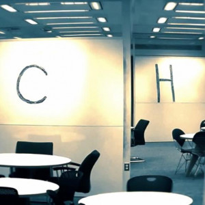 A graying image of a floor of Regenstein library with tables, chairs, and whiteboards. On the whiteboards, the letters E, C, H, and O are visible.