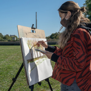 A student wearing a mask paints on an easel on a grassy field. The Unviersity of Chicago is in the background.