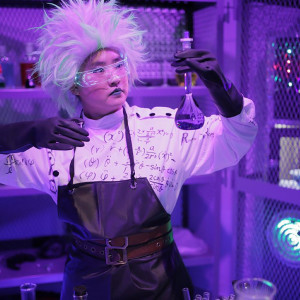 Performer in a laboratory set examines a beaker