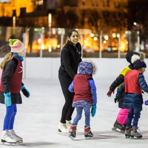 A smiling female student shows a group of five children how to skate on an ice rink at night. Warm lights illuminate UChicago campus buildings in the background.