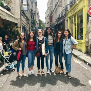 Six UChicago neuroscience students pose in the middle of a Parisian street lined with shops and cafés.