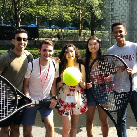 A group of five students post with a giant tennis rackets and an oversized tennis ball.