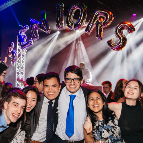 "A group of students poses at a party with the word ""Seniors"" spelled in balloons in the background."