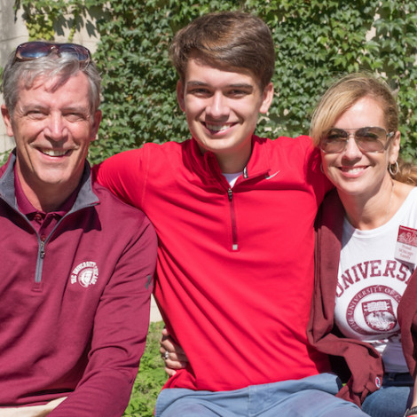 A male student poses with his parents, who are wearing UChicago apparel.