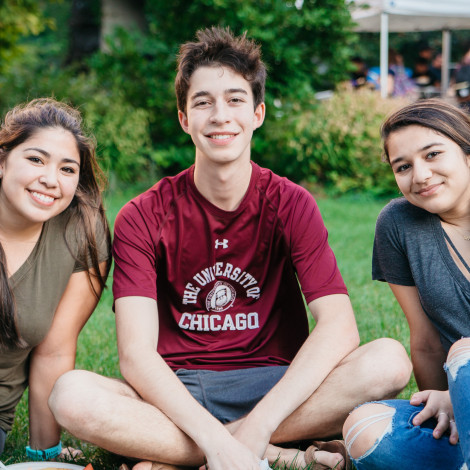 Three students sit on the grass during a barbecue.