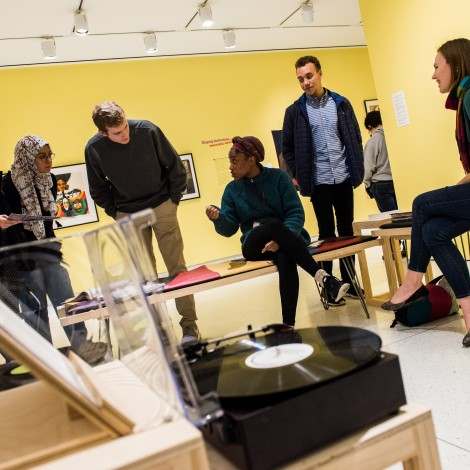 A group of four students sit listening to a record player with a professor in a yellow room in a museum.
