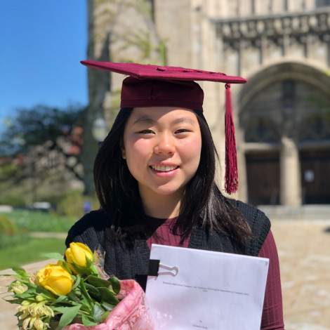 A portrait of Michelle Chong in cap and gown outside Rockefeller chapel.