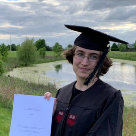 A portrait of Emily Stevens holding a paper copy of their BA thesis