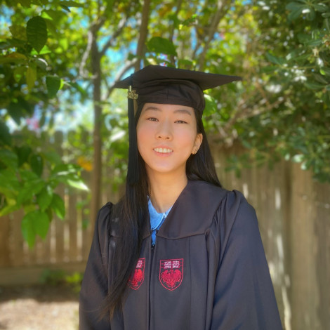 Ihna Yoo portrait outdoors in cap and gown.