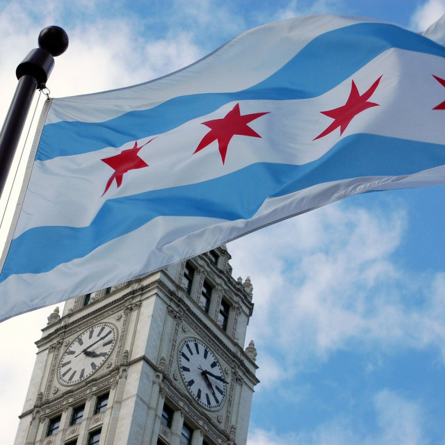 Chicago's flag flying in front of the Wrigley Building