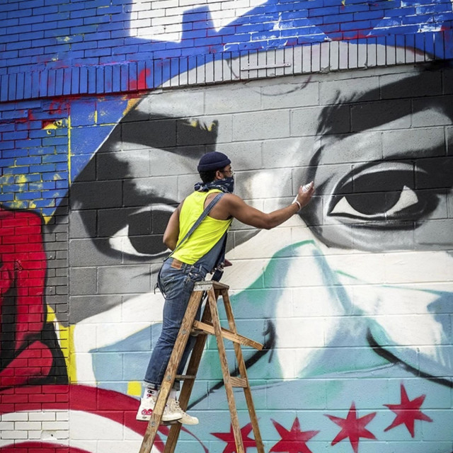 An artist paints a mural celebrating the heroism of Chicago's pandemic first responders