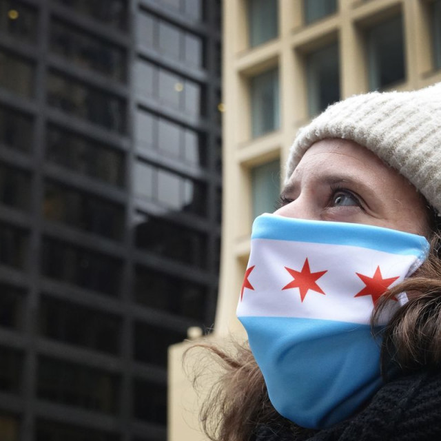 Student looks at Chicago's downtown while wearing a Chicago flag mask