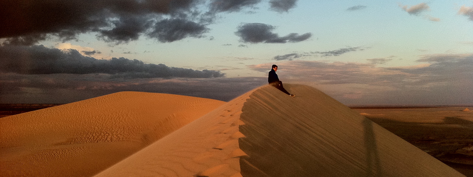 A solitary student sits atop a sand dune in the Sahara at sunset.
