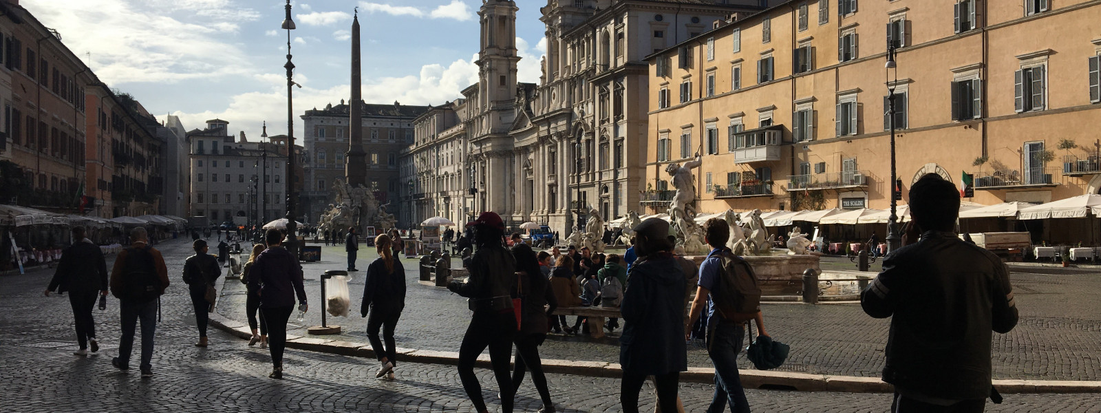 A line of students, in silhouette, walk through a public square in Rome.