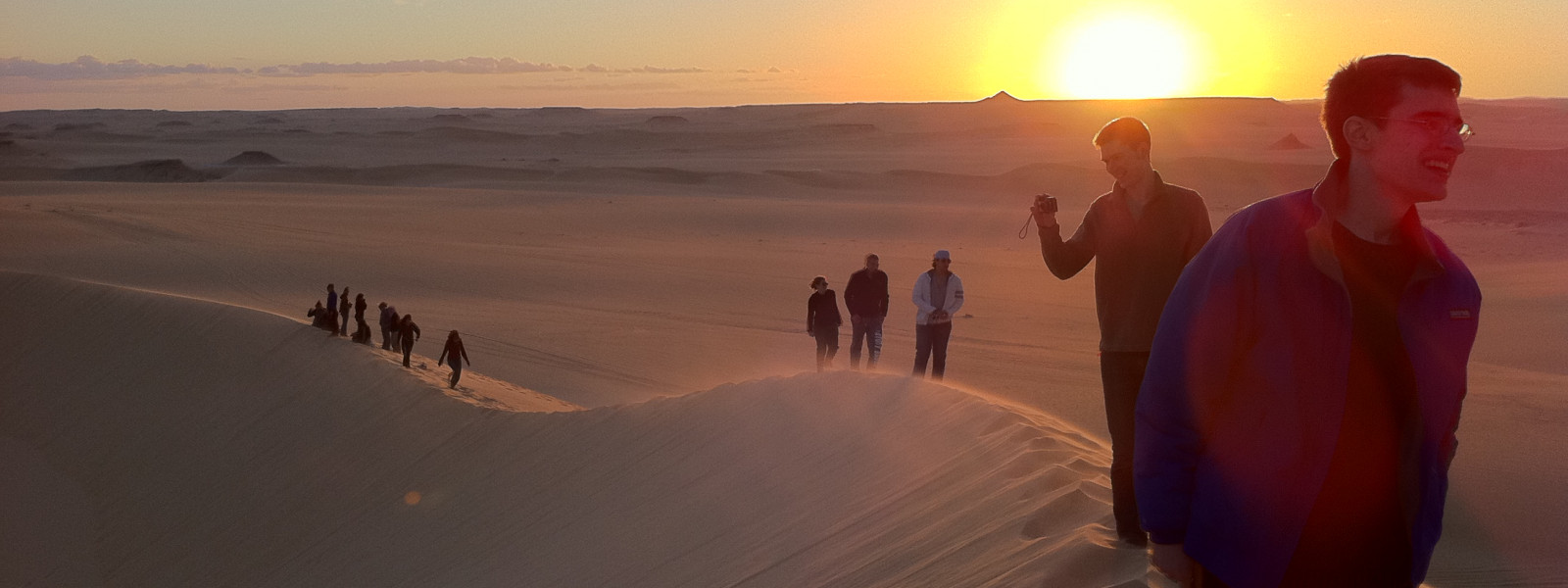Students walk in a line on a sand dune as the sun goes down.