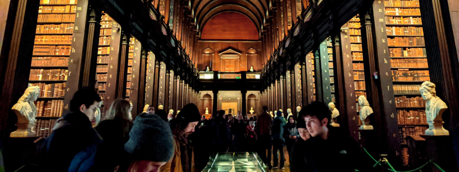 Visitors tour the wood-paneled library.